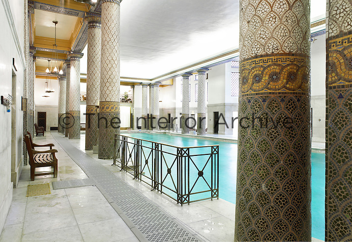 The interior of the London's Royal Automobile Club. An original feature of the historic structure, the pool 26 meters long and has a deck done in Sicilian white marble. The Doric columns are inlaid with multicolored mosaic patterns combining Greek sophistication with Roman-inspired splendor.