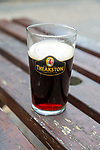 Part full pint glass of Theakston's Old Peculier beer cask real ale on table, UK