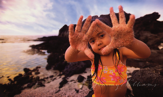 A little girl shows the camera that her hands are covered with sand while playing on the beach