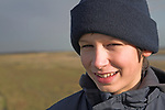 Portrait close up of smiling young teenage boy, UK outdoors wearing wool bobble hat