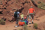 Mom and dad pulling children in wagons on a trail in Arches National Park, Moab, Utah, USA. .  John offers private photo tours in Arches National Park and throughout Utah and Colorado. Year-round.