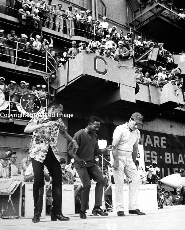 Hollywood comedian Bob Hope joins dancers Harold and Fayard Nicholas in a dance step aboard the U.S. aircraft carrier Ticonderoga. December  1965. (USIA)<br /> NARA FILE #:  306-MVP-8-4<br /> WAR &amp; CONFLICT BOOK #:  390