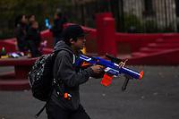 A boy plays with a toy gang at Manhattan's Chinatown in New York, Nov 11, 2013. VIEWpress/Eduardo Munoz Alvarez