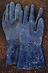 Heavy-duty blue rubber gloves spattered with paint or chemicals lying on rusty metal sheet