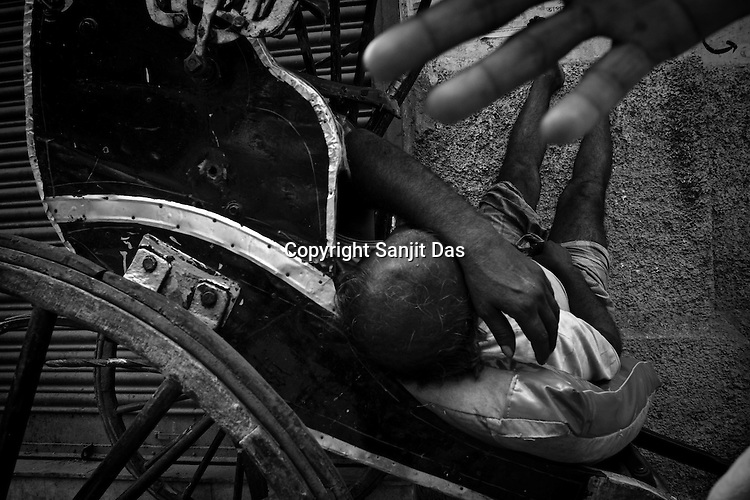 A rickshaw puller takes a nap on a summer afternoon in Calcutta, India. 93 out of every 100 rickshaw pullers are homeless. They sleep after the city sleeps and wake up before everyone else does. Many of them are the sole bread earners for their family. Many plus 40. Many minus any other specialisation for any other job. Of the twenty four thousand rickshaw pullers, only 387 have licenses. .Many rickshaw pullers earn a meagre wage of 100-150 rupees (US $ 2.25-3.5) a day of which they have to give a daily rickshaw rent of 60 (US$ 1.35) rupees to the agent at the end of the day.