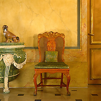 In the entrance hall an 18th century cane-backed chair with a cushion covered in a contemporary green velvet is situated in front of painted faux-marble walls