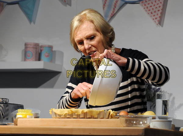Mary Berry .at the Cake International Show, Excel, London, April 12th 2013..half length live demo demonstration trade fair black and white striped stripy top sweater jumper cooking baking microphone bowl pie dish tart pouring cook pastry chef .CAP/PP/BK.©Bob Kent/PP/Capital Pictures