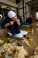 Keitarou Yokoyama checking the straightness of a piece of bamboo as part of the bow making process. Yokoyama Reimei Bowmakers, Miyakonojo, Miyazaki Prefecture, Japan, December 23, 2016. A handful of bowyers from the Kyushu city of Miyakonojo make over 90% of all the bows used in traditional Japanese archery. The bows are made from laminated bamboo and haze wood in process that consists of over 200 individual tasks. At over two meters from tip to tip the bows the longest used in the world.