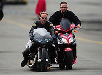 Nov. 12, 2011; Pomona, CA, USA; NHRA pro stock motorcycle rider Matt Smith (left) with a crew member during qualifying at the Auto Club Finals at Auto Club Raceway at Pomona. Mandatory Credit: Mark J. Rebilas-.