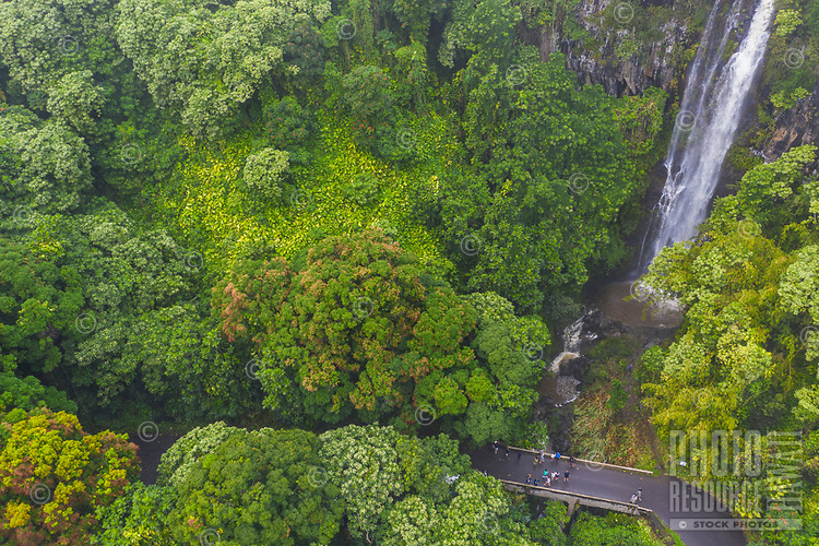 A group of sightseers take a closer look at a waterfall along the road to Hana, Maui.