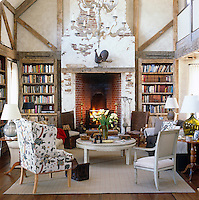 A sofa and assorted armchairs are arranged around the large fireplace in this library/sitting room