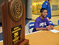 STAFF PHOTO BEN GOFF  @NWABenGoff -- 12/05/14 Austin Salazar waits for a signing ceremony to begin, with Rogers High's 2014 Boys' cross country state championship trophy sitting nearby, in the commons at Rogers High on Friday Dec. 5, 2014.