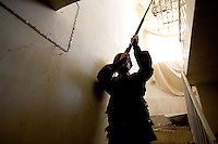 An Iraqi Minister of Interior Special Police Commando from  2nd Company, 2nd Battalion, 2nd Brigade searches a house while supporting the US military in a civil affair operation with the purpose of verifying progresses made by iraqi contractors renovating the Mul'Hab secondary school in Eastern Ramadi, Al Anbar Province, Iraq on Tuesday Feb 07 2006. Suspected insurgents were reported to attack US positions from this house. The US command sent the Iraqi Commandos to search and clear it.  2nd Company came under fire during the operation returning several hundred of rounds back to the insurgents that were approaching them on civilian vehicles armed with machine guns and Rocket propelled grenades. An American gun truck was slightly damaged when an RPG hit close by. The insurgency operates extensively in the Mul'Hab neighborhood attacking the coalition  and  Iraqi forces on a regular  bases.