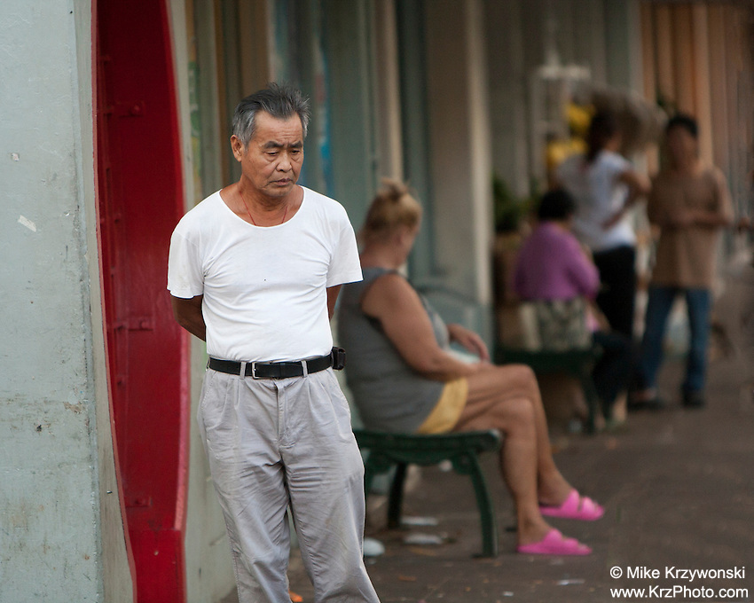 Elderly Asian man standing on sidewalk in Chinatown, Downtown Honolulu, Oahu, Hawaii