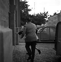 """Affaire de la """"Tournerie des drogueurs""""  JUIN 1961<br /> <br /> Devant l'entrée de la prison Saint-Michel. 3 juin 1961. Arrivée de Marie-Thérèse Davergne (accusée) à la prison : elle vient de sortir de la fourgonnette et court vers l'entrée (vue de dos), elle est en partie cachée par un homme qui la suit (vue de dos) . Cliché pris dans le cadre de l'affaire de la """"Tournerie des drogueurs"""" dont le procès s'est ouvert à Toulouse le 5 juin 1961. Observation: Affaire de la """"Tournerie des drogueurs"""" : Procès qui s'est ouvert aux assises de Toulouse le 5 juin 1961, sous la présidence de M. Gervais (conseiller doyen). Sur le banc des accusés se trouvent François Lopez, Raoul Berdier, Marie-Thérèse Davergne (Maïté) et d'autres malfaiteurs toulousains (Camille Ajestron, Henri Oustric, Raymond Peralo, Marcel Filiol, Paul Carrère, Charles Davant et François Borja). Outre les accusations pour association de malfaiteurs, ils comparaissent pour l'assassinat de Jean Lannelongue, propriétaire du Cabaret la Tournerie des Drogueurs (rue des Tourneurs) dans la nuit du 3 au 4 janvier 1959, au cours d'une tentative de racket."""