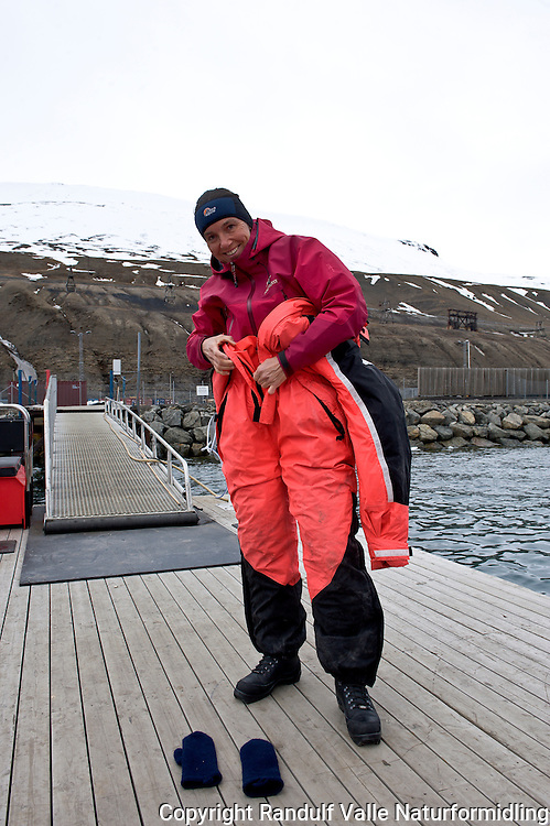 Dame tar på overlevelsesdrakt. ---- Woman putting on survival suit.