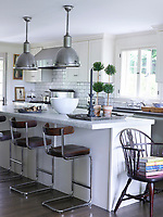 In the kitchen, the island has a top of honed Carrara marble, the wall tiles are by Waterworks, the stove is Viking, and the stools are by York Street Studio; the 19th-century Windsor chair is a family heirloom, and the 1920s English pendants are from BK Antiques.