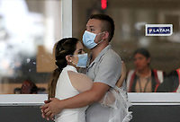 "BOGOTA, COLOMBIA - March 12:  A couple hug as they wear face masks around the International airport ""El Dorado"" on March 12, 2020 in Bogota, Colombia. The World Health Organization declared a global pandemic as the coronavirus rapidly spreads across the world. Colombian President Ivan Duque declared a health emergency to contain an outbreak of coronavirus, suspending public events with more than 500 people. (Photo by Daniel Munoz/VIEWpress)"