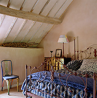 A Victorian iron bedstead has been painted oxblood red and covered with a series of Indian cotton quilts in this attic bedroom
