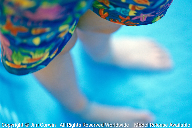 Girl ( 9 yrs old) wading in small pool close-up of colorful shorts and legs and feet, summer fun, Lake Pleasant, Bothell, Washington State USA      MR