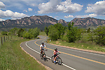 Father and son biking on rural, mountain road in Boulder, Colorado .  John leads private photo tours in Boulder and throughout Colorado. Year-round.