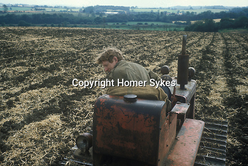 Man driving old tractor 1980s Britain. UK.