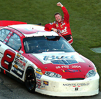 Dale Earnhardt Jr. pumps his fist in victory upon emerging from his Budweiser race car after winning the Daytona 500 at the Daytona International Speedway.