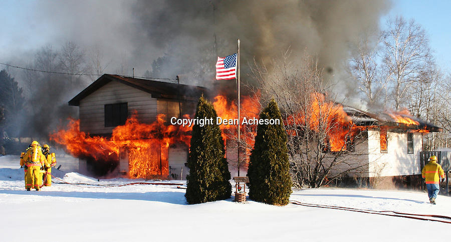 Fire destroys a home Jan. 19, 2005, in Crandon, Wis. as firefighters wait for hoses to be pressurized with water. The house was already engulfed by the time firefighters arrived. No one was home at the time.