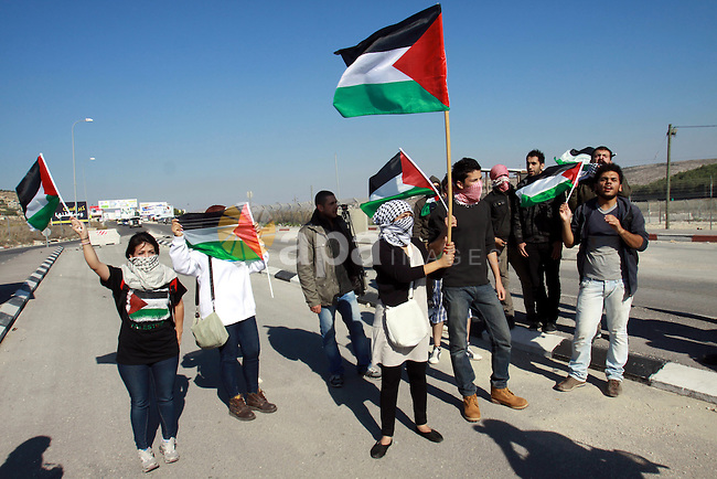 Palestinian activists hold their national flags while they block a road leading to Huwwara checkpoint near the West Bank city of Nablus during a demonstration in support of the people of the Gaza Strip and against Israeli air strikes on November 15, 2012. Several Palestinians were killed following a series of Israel's concurrent airstrikes on Gaza city, among them was Ahmed al-Jaabari, top commander of Hamas armed wing Al-Qassam brigades, and more than 150 others wounded, government's emergency services in the Gaza Strip said. Photo by Nedal Eshtayah