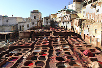 General view of the Chouara tannery, Fez, Morocco, pictured on February 22, 2009 in the morning. The Chouara tannery is the largest of the four ancient tanneries in the Medina of Fez where the traditional work of the tanners has remained unchanged since the 14th century. It is composed of numerous dried-earth pits where raw skins are treated, pounded, scraped and dyed. Tanners work in vats filled with various coloured liquid dyes derived from plant sources. Colours change every two weeks, poppy flower for red, mint for green, indigo for blue, chedar tree for brown and saffron for yellow. Fez, Morocco's second largest city, and one of the four imperial cities, was founded in 789 by Idris I on the banks of the River Fez. The oldest university in the world is here and the city is still the Moroccan cultural and spiritual centre. Fez has three sectors: the oldest part, the walled city of Fes-el-Bali, houses Morocco's largest medina and is a UNESCO World Heritage Site;  Fes-el-Jedid was founded in 1244 as a new capital by the Merenid dynasty, and contains the Mellah, or Jewish quarter; Ville Nouvelle was built by the French who took over most of Morocco in 1912 and transferred the capital to Rabat. Picture by Manuel Cohen.