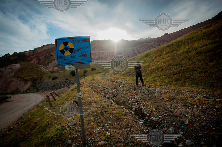 A man passes a sign that reads: 'Attention! Radioactivity Dangerous for Life' at radioactive mining waste Dump No7. Local environmentalists are concerned that there is a chance that arsenic beneath the dumps is leaking into the Mailuu-Suu River.