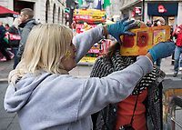 A street vendor applying facepaint to a Wales fan<br /> <br /> Photographer Simon King/CameraSport<br /> <br /> International Rugby Union - 2017 Under Armour Series Autumn Internationals - Wales v Australia - Saturday 11th November 2017 - Principality Stadium - Cardiff<br /> <br /> World Copyright &copy; 2017 CameraSport. All rights reserved. 43 Linden Ave. Countesthorpe. Leicester. England. LE8 5PG - Tel: +44 (0) 116 277 4147 - admin@camerasport.com - www.camerasport.com
