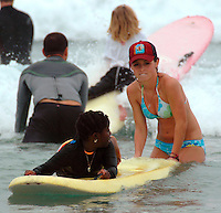 "Saturday, August 23 2008.  Maddie Rupp helps ""Chare"" (no last name given) into a wave while fellow volunteer Jeff Lhuillier (background) heads out through the surf with his daughter Emma (6) during the 22nd Annual Kids Day hosted by the Windansea Surf Club at La Jolla Shores.  Lhuillier, a French native who usually does the cooking at the annual event, took a break to give his daughter a quick surf lesson."