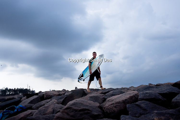 "Gaura Gopal, one of the Krishna devotees from the Kaliya Mardana Krishna Ashram is seen walking on the rock jetty of the Arabian Sea on the beach front of Mangalore, Karnataka, India.  ..Krishna devotees in the Gaudiya Vaishnava tradition of Hinduism, they are known collectively as the ""surfing swamis."" The ""surfing ashram"" is growing in popularity and surfing here is a form of meditation, a spiritual practice leading to heightened states of awareness."