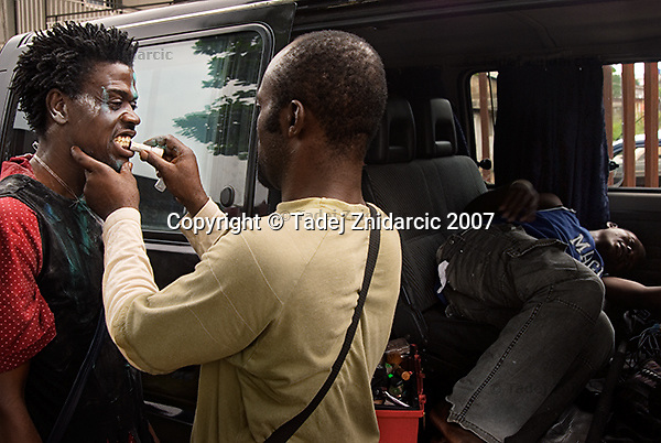 Make-up artist Kpoyi Creation (right) puts black paint on the teeth of actor Jeffery Adakah (left) playing a madman on the set of a Nollywood movie production. The elements of magic, witchcraft and madness are common in Nollywood films.