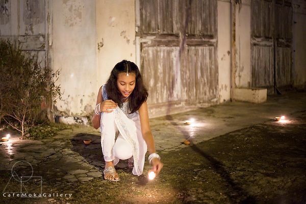 Beautiful young Trinidadian girl in white lighting a deya Divali,Hindu festival of light,