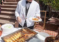 A waiter from Barbetta serves vegetable filled cannoli after the unveiling of the new wayfinding kiosks stand at either end of Restaurant Row in New York, West 46th street between 8th and 9th Avenues, on Tuesday May 16, 2017. At least four years in the making the illuminated kiosks show the names of the many eateries that populate the street. The unveiling is just in time for the Taste of Times Square event taking place on the street on June 5. (© Richard B. Levine)