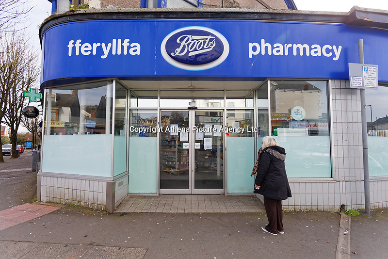 Pictured: A woman stands in front of the doors of the closed Boots pharmacy in the Uplands area in Swansea, Wales, UK. Saturday 21 March 2020<br /> Re: Covid-19 Coronavirus pandemic, UK.