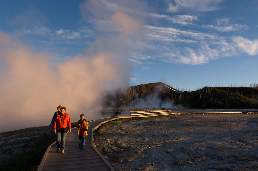 Park visitors walk through the sunset-colored steam cloud of the Excelsior Geyser Crater in Yellowstone National Park, Monday, May 30, 2005. (Kevin Moloney for the New York Times)