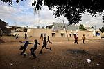 Eritrean asylum-seeker youth play football near their temporary shelter in southern Tel Aviv, Israel.