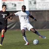 University of Connecticut midfielder George Fochive (9) brings the ball forward as Northeastern University forward Donovan Fayd'Herbe de Maudave (9) defends..NCAA Tournament. University of Connecticut (white) defeated Northeastern University (black), 1-0, at Morrone Stadium at University of Connecticut on November 18, 2012.