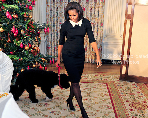 First lady Michelle Obama walks Bo in the State Dining Room of the White House during an event with military children at the preview of the White House Christmas decorations in Washington, DC. The theme for the White House Christmas 2011 is Shine, Give, Share - celebrating the countless ways we can lift up those around us, put our best self forward in the spirit of the season, spend time with friends and family, celebrate the joy of giving to others, and share our blessings with all.  The theme translates to the holiday décor on several levels. There is the literal translation through the use of shiny elements – star motifs, quartz and metallics like copper, aluminum and mirrored paper. There is also a conceptual connection – we're inviting visitors to give their thanks to members of our military, and have once again invited guest artists to share their talents working with the White House. This year's décor also includes handmade decorations crafted from simple materials – paper, felt, and even recycled cans. These are projects that anyone can do at home using readily available materials that are inexpensive or free..Credit: Ron Sachs / CNP