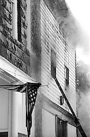The American flag hangs wet, limp and twisted as firefighters battle a blaze nextdoor in Sturgis, South Dakota in the early 1990s.
