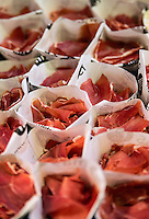 Dried ham snacks for sale by vendor in La Boqueria market, Barcelona, Spain