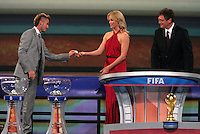 David Beckham hands a ball to Charlize Theron as FIFA general secretary Jerome Valcke looks on during the FIFA Final Draw for the FIFA World Cup 2010 South Africa held at the Cape Town International Convention Centre (CTICC) on December 4, 2009.
