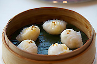 China, Hong Kong S.A.R..The Ritz-Carlton, Hong Kong. World's highest Dim Sum at Tin Lung Heen. Golden shrimp dumplings with bamboo shoots and asparagus.