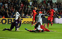 Pictured: Wilfried Bony of Swansea (C) fails to score after being  is tackled by Martin Skrtel of Liverpool (R), goalkeeper Simon Mignolet looks on (L). Monday 16 September 2013<br /> Re: Barclay's Premier League, Swansea City FC v Liverpool at the Liberty Stadium, south Wales.