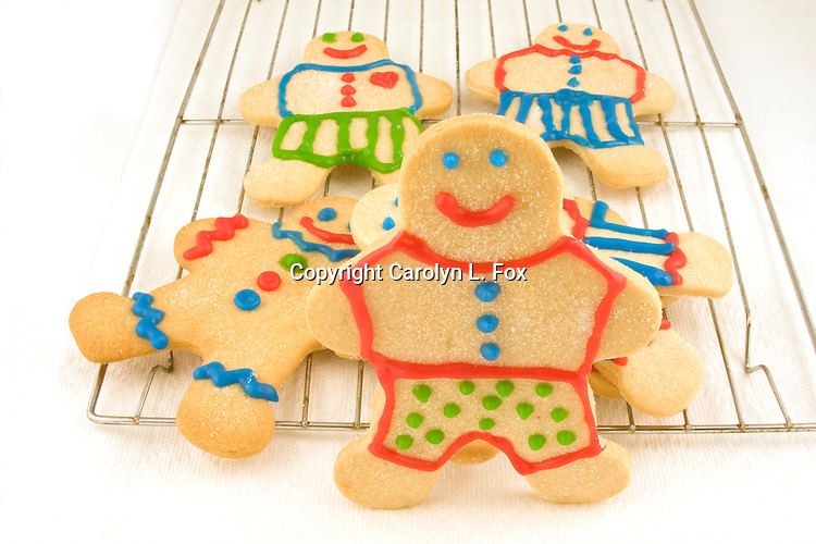A cooling rack holding four sugar cookie men is laying on a table.   One sugar cookie man is standing in front of the cooling rack.