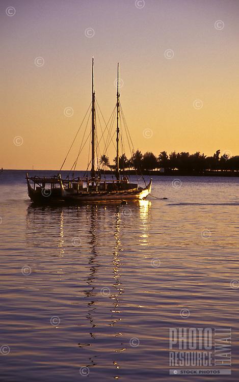 Hawaiian sailing canoe off the coast of Ala Moana beach park, island of Oahu at sunset