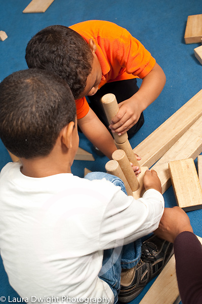 Education preschool 4 year olds two boys building together with wooden blocks